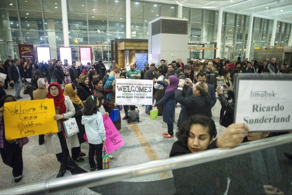 Members of groups who are sponsoring two Syrian refugee families hold up signs welcoming their charges as they wait for the families to arrive at Toronto's Pearson Airport, on Wednesday, Dec. 9, 2015. THE CANADIAN PRESS/Chris Young